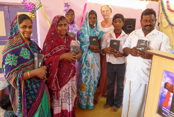 Grateful church members holding new bibles