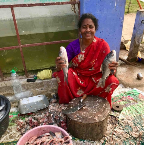 Lady selling fish by the riverside