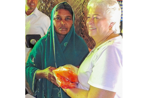 Pat giving sari to widow in India