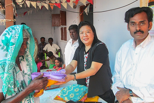 Singapore team member giving a sari to a poor widow