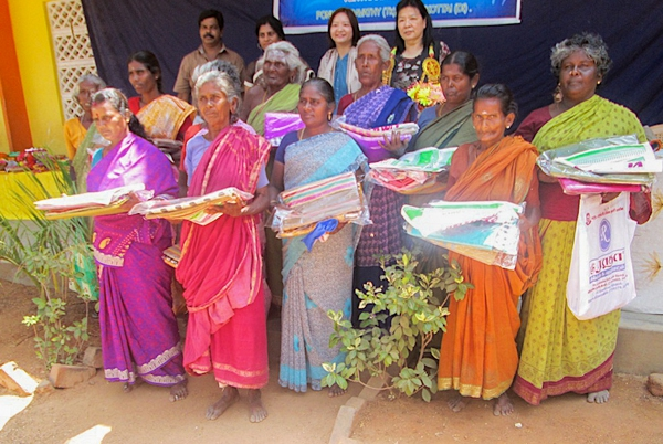 Singapore Mission team members together with grateful widows holding their saris