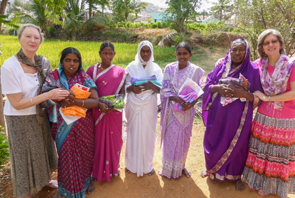 Team members in group with grateful widows holding new saris