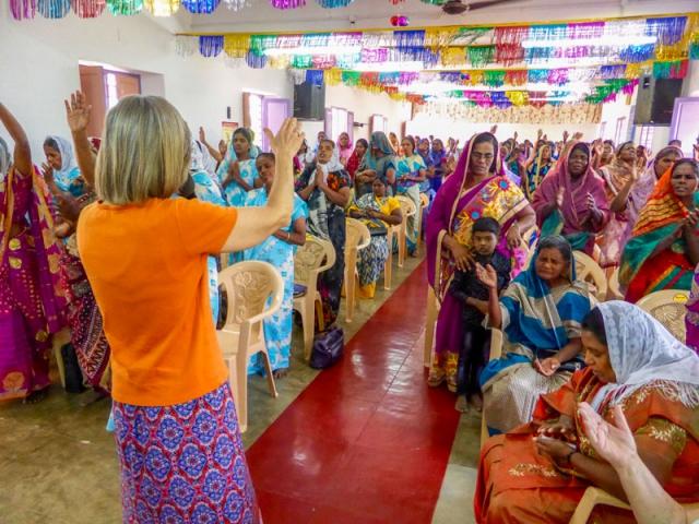 Kym praying at women's meeting