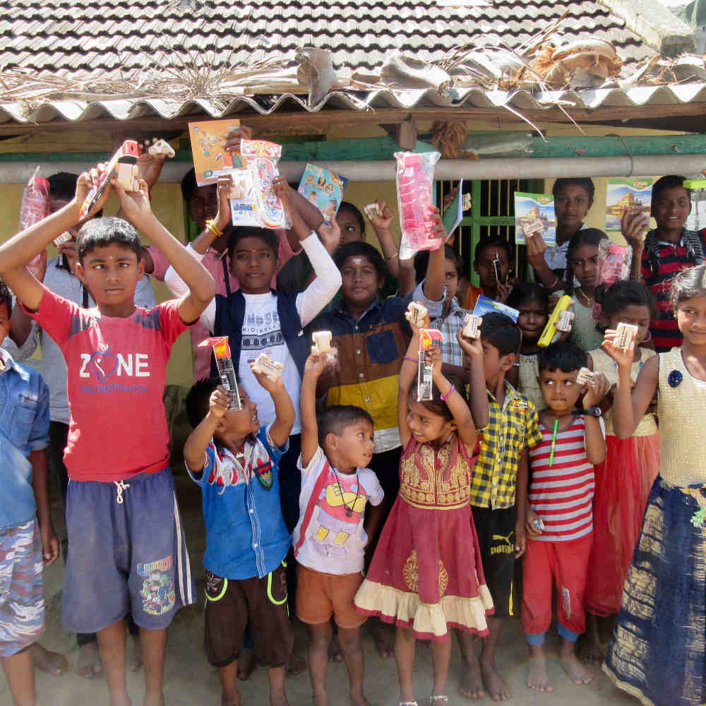 Happy thankful children holding up their educational gifts