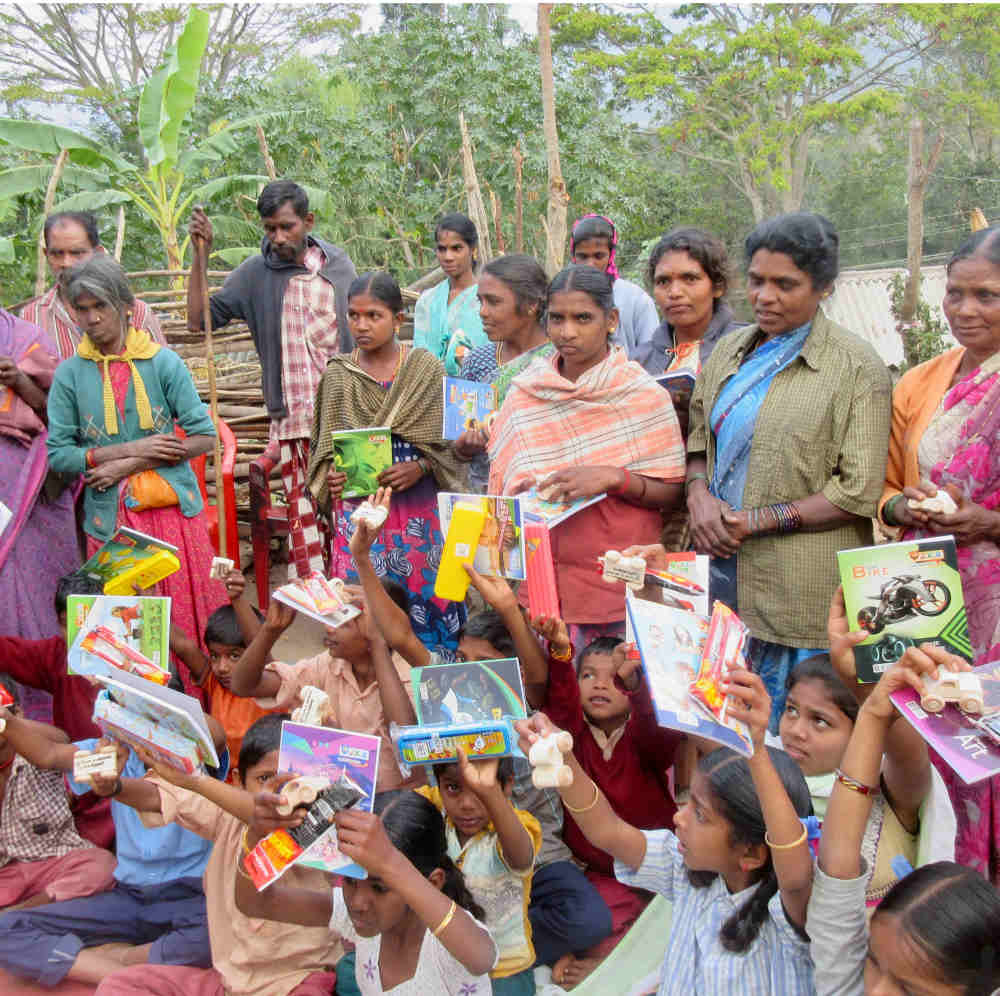 Happy tribal village children holding up their educational gifts
