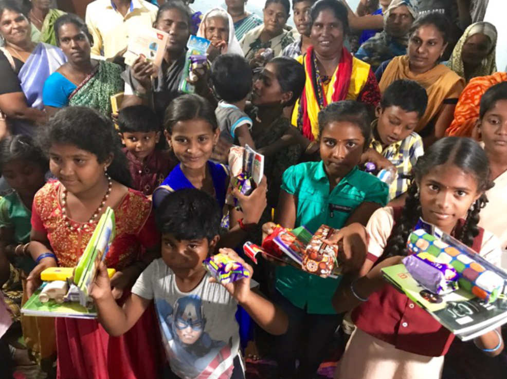 Happy children and church members with gifts