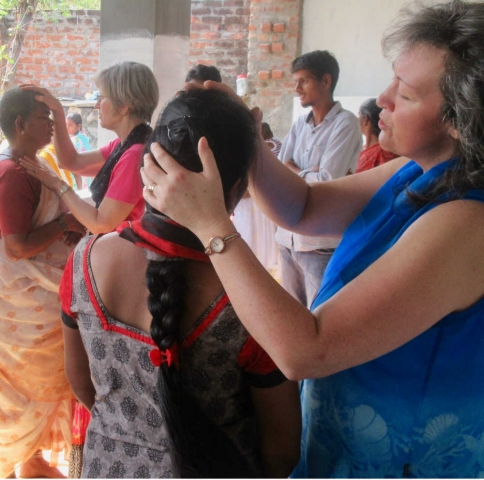 Mission team praying for healing after Sunday church service