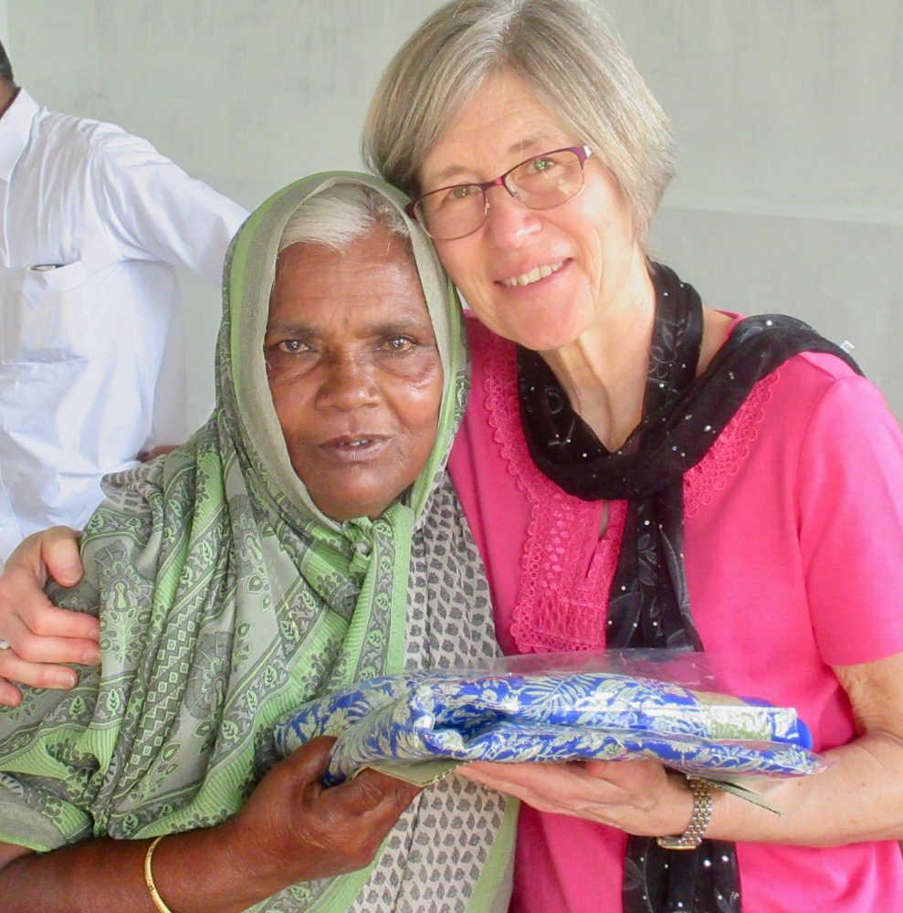 Kym giving elderly widow a new sari