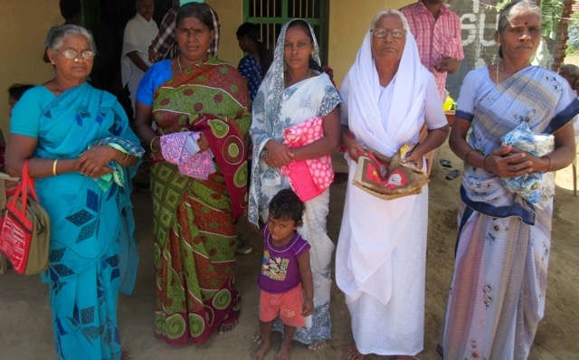 Group of thankful widows holding their new saris