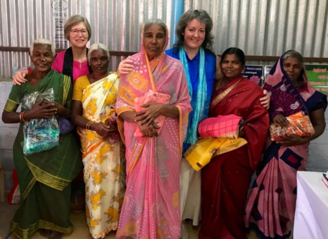 Pam and Kym with group of widows holding their new saris