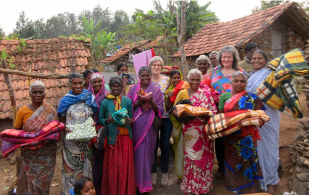 Happy tribal villagers holding their new blankets