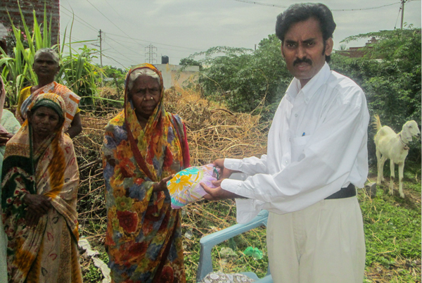 Pastor David giving new sari to widow in India