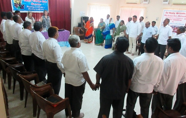 IVCM Pastors standing in prayer together during group meeting