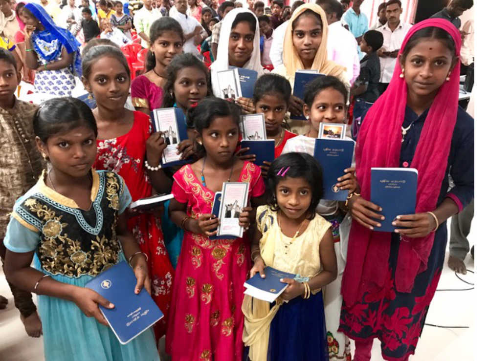 New believers holding their new testaments after youth meeting