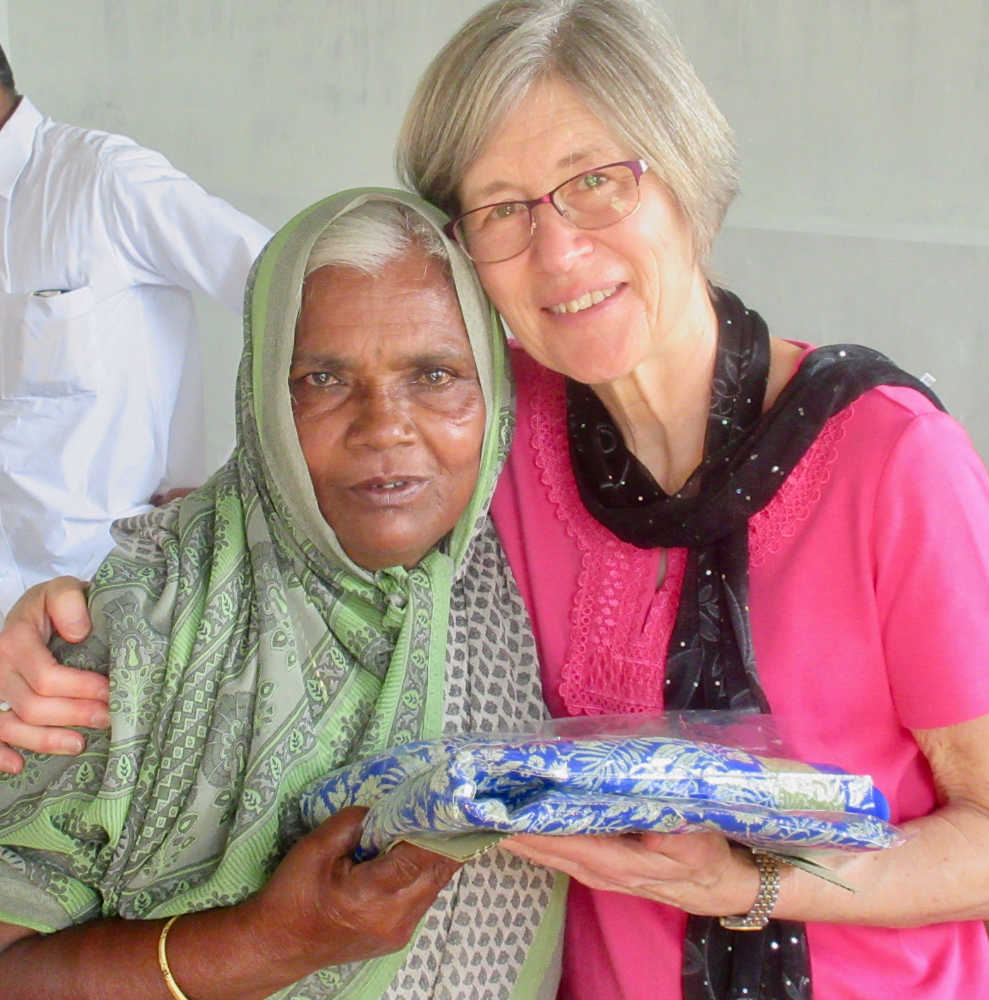Kym giving elderly widow a new sari