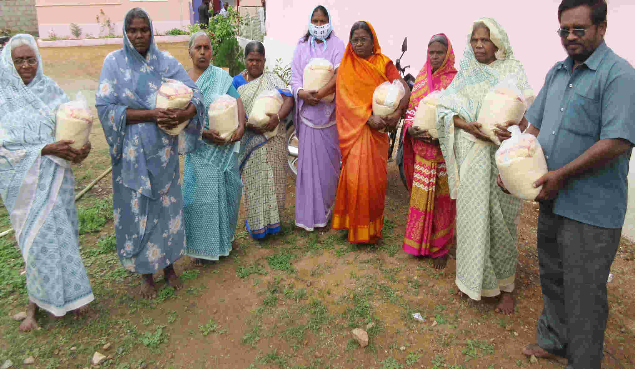 Ladies holding bags of rice